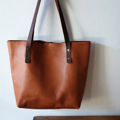 """"""" C L A S S I C """" Leather Tote Bag in BROWN  -This bag made from soft chamois leather, which has got a nice texture.   -This treated/coated leather is very durable and more resistance, will not leave the stain from light rain or water.  -Strong strap made from 3.5 mm thickness-oiled leather, perfect for carrying over the shoulder.  -The interior bag made from genuine leather, and a key fob.  -A magnetic closure to keep your stuffs in place.  -Roomy and strong enough to hold a laptop and other essentials.  -Light-weight. .................................................. SPECIFICATIONS: ( approx )  Size: Width 12 (bottom),16 (top) x Height 12 x Depth 4 inch  Handle Drops : 10 inches / 25 cm high, 2 cm wide, 3.5 mm thickness Colour: BROWN Material: Genuine Chamois Leather  ..................................................  Due to the nature of leather, mark, colors, and texture may slightly different in each piece.  **This tote is MADE TO ORDER, will take around 10 days for production. ..................................................  Thank you for visiting!"""